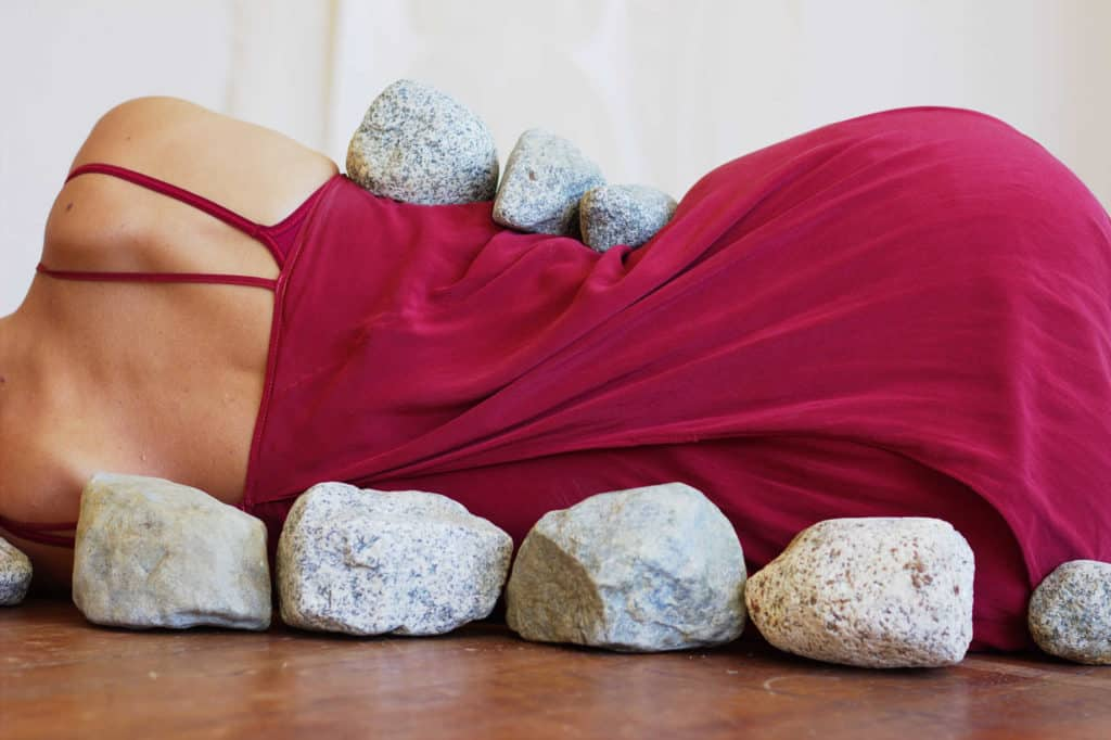 Rocks aligning curvature of woman's back