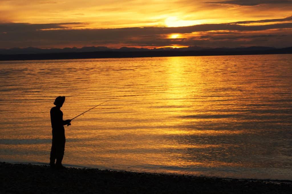 Fisherman at orange sunset casting his line